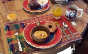 Omelet with veggies and pork, local peaches and peach juice, buttered bagel and strawberry jam